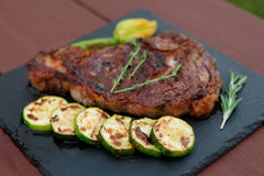 Rib eye steak with vegetables on a slate plate Royalty Free Stock Photo