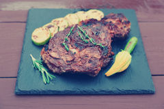 Rib eye steak with vegetables on slate plate, toned Royalty Free Stock Images