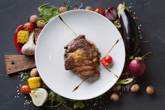 Rib eye steak on white plate with vegetables border on dark background Stock Photography