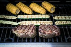 Rib eye steak with zucchini and corn on gas grill Royalty Free Stock Image