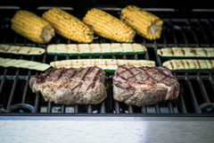 Rib eye steak with zucchini and corn on grill Stock Image
