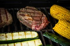 Rib eye steak with zucchini and corn on grill, soft focus Royalty Free Stock Photos