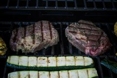 Rib eye steak with zucchini on grill, top view Royalty Free Stock Photo