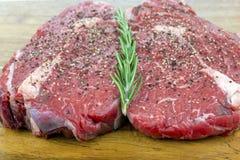 Rib Eye Steaks cru poivron sur un conseil en bois Photos stock