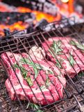 Rib eye steaks and grill with burning fire behind them. Stock Photo