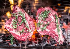 Rib eye steaks and grill with burning fire. Stock Photo