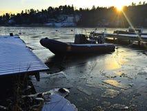 Rib la barca in lago congelato con il sole che va giù fotografia stock libera da diritti