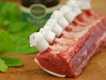 Rib of Lamb. Rib of British Lamb on butcher's block with fresh mint and mint sauce royalty free stock photography