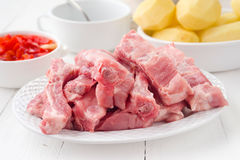 Rib pork sliced and peeled potatoes in earthenware Stock Images