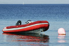 RIB, rigid inflatable boat moored at buoy. In a calm bay Royalty Free Stock Photo