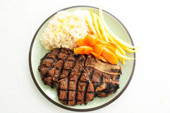 Rib steak with creamy risotto, carrots and Royalty Free Stock Image