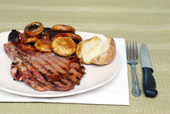 Rib Steak with mushrooms and a baked potato Royalty Free Stock Photo