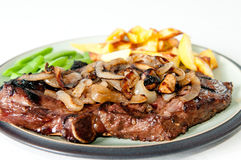 Rib steak and onions. Rib steak with sauteed mushrooms and onions, french fries and vegetables Royalty Free Stock Photos