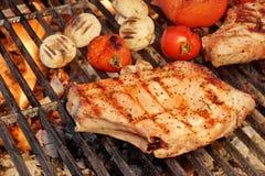 Rib Steak, pomodori e funghi arrostiti barbecue sulla griglia calda Immagini Stock