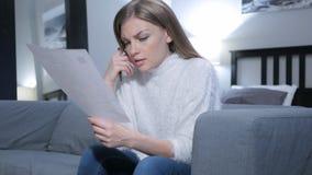 Ribaltamento della donna dopo la lettura dei documenti, ritenenti tristi fotografia stock libera da diritti
