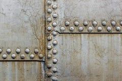 ribattini arrugginiti del primo piano su un fondo grigio Fotografia Stock