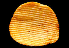 Ribbed potatoes chips on black Royalty Free Stock Photography