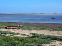 ribble出海口的看法lancashire的与在河的一小渔船和和在岸的老遗弃快艇 库存照片
