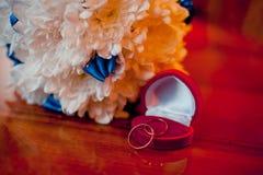 Γαμήλια δαχτυλίδια σε ένα άσπρο υπόβαθρο με μια ανθοδέσμη του μπλε ribbo Στοκ Εικόνες
