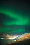 Ribbon of Aurora polaris. Polar lights tape over a mountain valley stock photography