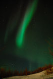 Ribbon of Aurora polaris. Above the slope of burrow royalty free stock images