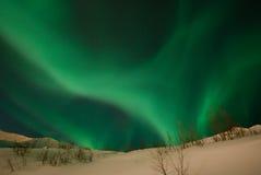 Ribbon of Aurora polaris. Aurora polaris above the slope of mountain stock photography