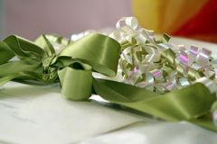 Ribbon and Bow. Selective focus green, silver and purple gift wrapping bow and ribbon. Package also has out of focus greeting card envelope royalty free stock photos