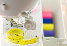 Ribbon, colored thread and sewing machine. The process of working seamstresses stock photo