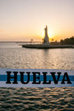 Ribbon with the colors of Huelva and in the background out of focus, the Columbus Monument. Sunset on the Punta del Sebo. In the foreground, ribbon of blue and Royalty Free Stock Photo