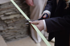 Ribbon cutting ceremony. A man with scissors cutting the ribbon at the opening ceremony Royalty Free Stock Photo
