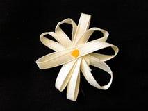 Ribbon Daisy with Yellow Center. Daisy made from white ribbon with yellow center on black background Royalty Free Stock Photography