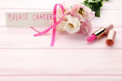 Ribbon with flowers, pomade. Pink ribbon with flowers, pomade and inscription Breast Cancer on wooden table Stock Photography
