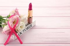 Ribbon with flowers and pomade. Pink ribbon with flowers and pomade on wooden table Stock Photo