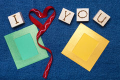 Ribbon heart, love inscription on wooden cubes, photo frame and Royalty Free Stock Images