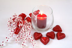 Ribbon, lit candle and chocolate hearts. Royalty Free Stock Photo