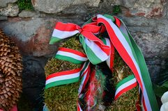 Ribbon with national colours of Hungary tied up to the flower tribute standing near to the old castle wall in Mukachevo, Ukraine. Ribbon with national colours Royalty Free Stock Images