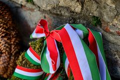 Ribbon with national colours of Hungary tied up to the flower tribute standing near to the old castle wall in Mukachevo, Ukraine. Ribbon with national colours Stock Photo
