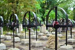 Ribbon with national colours of Poland tied up to the old cross on the cemetery. Memory of victims day concept. Stock Photography