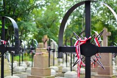 Ribbon with national colours of Poland tied up to the old cross on the cemetery. Warsaw uprising concept. Ribbon with national colours of Poland tied up to the Stock Photos