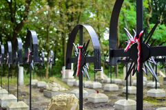 Ribbon with national colours of Poland tied up to the old cross on the cemetery. Uprising concept. Ribbon with national colours of Poland tied up to the cross Royalty Free Stock Photos