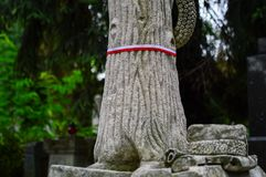 Ribbon with national colours of Republic of Poland tied up to the old monument on the cemetery. National memory day concept. Stock Photography