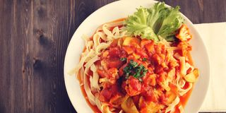 Ribbon pasta with Arrabiata sauce. Vegetarian dish. Ribbon pasta with Arrabiata sauce. Close up. Mediterranean dish. Tagliolini pasta with vegetables stock photo