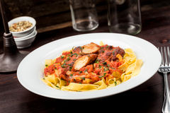 Ribbon pasta with chicken and tomato leek sauce. Topped with chives royalty free stock image