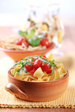 Ribbon pasta and peeled tomato. Ribbon pasta and diced tomato topped with arugula stock images