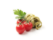 Ribbon pasta and tomatoes. Cooked ribbon pasta and fresh tomatoes - studio stock image