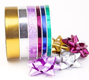 Ribbon reel with colorful ribbons and bows. A reel of colorful ribbons and bows on a white background Royalty Free Stock Image