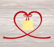 A ribbon in the shape of a heart. Empty Yellow sheet of paper fo. R notes. Sticker. Red bow. Greeting card or invitation for a holiday. St. Valentine`s Day Royalty Free Stock Image