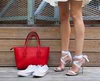 Ribbon Tie Stilleto shoe, sneakers and fashionable big red handbag. Fashionable woman with long beautiful legs standing Stock Photos
