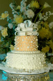 Ribbon topped Wedding Cake. A ribbon topped wedding cake sits on a silver server and is backed by a flower arrangement Stock Photography