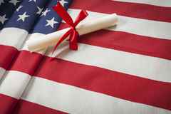 Ribbon Wrapped Diploma Resting on American Flag with Copy Space Royalty Free Stock Image
